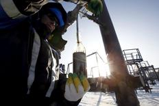 A worker takes oil samples from a well at the Gazpromneft-owned Yuzhno-Priobskoye oil field outside the West Siberian city of Khanty-Mansiysk, Russia, in this January 28, 2016 file photo.  REUTERS/Sergei Karpukhin/Files