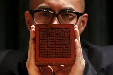 "A seal bearing the inscription ""Revere Heaven and Serve thy People"", carved for the Kangxi Emperor, is displayed by Sotheby's Asia Deputy Chairman Nicholas Chow at a preview in Hong Kong, China in this March 14, 2016 file photo. REUTERS/Bobby Yip"