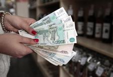 Продавец в магазине показывает росийские рубли. Рубль подорожал при открытии биржевых торгов пятницы на фоне текущей позитивной динамики нефти, в течение дня влияние на динамику будут оказывать и внутренние денежные потоки при бедном событиями сегодняшнем внешнем новостном фоне. REUTERS/Eduard Korniyenko