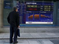 Un hombre mira un tablero electrónico que muestra el índice Nikkei, afuera de una correduría en Tokio, Japón. 2 de marzo de 2016. El índice Nikkei de la bolsa de Tokio subió el viernes en una sesión volátil, revirtiendo unas pérdidas iniciales luego de que el dólar se fortaleció frente al yen, pero una fuerte caída de las acciones de Fast Retailing limitó las ganancias. REUTERS/Thomas Peter