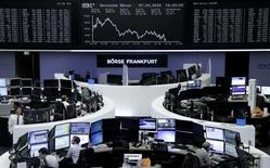 Traders work at their desks in front of the German share price index, DAX board, at the stock exchange in Frankfurt, Germany, April 7, 2016.     REUTERS/Staff/Remote
