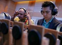 """Imagen de archivo de unas perdonas probando unos audífonos en la feria de sonido CanJam en Singapur, feb 21, 2016. Un enorme incremento en las ganancias por los servicios de """"streaming"""" ayudó a revertir el año pasado un declive de casi dos décadas en los ingresos de la música ya que el dinero originado por formatos digitales superó a las ventas físicas por primera vez, dijo el martes la asociación comercial IFPI. REUTERS/Edgar Su"""