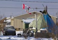 A tattered Canadian flag flies over a teepee in Attawapiskat, Ontario, in this file photo taken December 17, 2011. REUTERS/Frank Gunn/Pool/Files