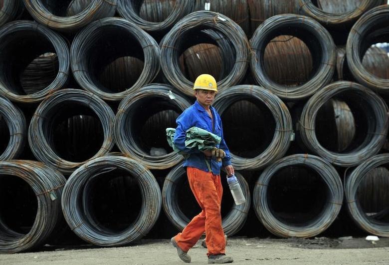2013年7月15日,辽宁沈阳一家钢材市场,一名工人经过成堆的钢筋。REUTERS/Stringer