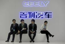 Staff members sit in front of a Geely signage at Auto China 2014 in Beijing in this April 20, 2014 file picture. REUTERS/Jason Lee/Files