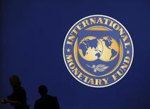 Люди на фоне логотипа МВФ в Токио 10 октября 2012 года. Казахстан, столкнувшийся со снижением доходов из-за падения цен на нефть, не планирует вести переговоры с Международным валютным фондом о возможных займах, ждет технической помощи для перехода к инфляционному таргетированию после девальвации тенге в прошлом году, сказал Рейтер глава Нацбанка Данияр Акишев. REUTERS/Kim Kyung-Hoon