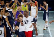 Kobe Bryant (front R) of NBA's Los Angeles Lakers interacts with Chinese students during a promotional event in Shanghai, July 31, 2014. REUTERS/Aly Song