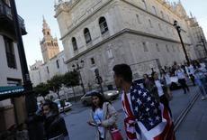 Exceltur, la patronal de las principales empresas turísticas en España, ha revisado al alza sus previsiones de crecimiento para este año ante la redistribución de los turistas entre diversos destinos mediterráneos tras una serie de atentados en el norte de África y Turquía. En la imagen, un hombre envuelto en una bandera estadounidense mira la Giralda en Sevilla, el 4 de marzo de 2016. REUTERS/Marcelo del Pozo