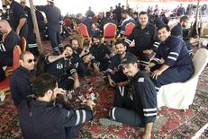 Kuwaiti oil sector employees sit in a shaded area on the first day of an official strike called by the Oil and Petrochemical Industries Workers Union over public sector pay reforms, in Ahmadi, Kuwait. REUTERS/Stephanie McGehee