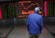 Un inversor mira un tablero electrónico que muestra la información de las acciones, en una correduría en Pekín, China, 15 de febrero de 2016. Las acciones chinas cerraron el martes con un leve avance, en momentos en que los inversores sopesan señales contradictorias sobre el camino de la recuperación económica de China. REUTERS/Kim Kyung-Hoon
