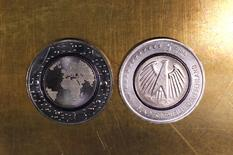 The new German commemorative five euro coin 'Planet Erde' ('Planet Earth') with a blue polymer ring, is displayed in Frankfurt, Germany, April 14, 2016. REUTERS/Kai Pfaffenbach/File Photo