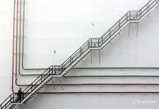 Рабочий поднимается по лестнице нефтехранилища на НПЗ MOL в Сазхаломбатте, Венгрия 9 января 2007 года. Средняя индикативная цена на нефть в будущем году составит $65 за баррель, прогнозирует первый замминистра энергетики России Алексей Текслер. REUTERS/Laszlo Balogh
