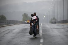 Un refugiado sirio besa a su hija mientras camina a través de una fuerte lluvia hacia la frontera con Macedonia, cerca de la ciudad griega de Idomeni. 10 de septiembre de 2015. La agencia Associated Press ganó el Premio Pulitzer por servicio público por sus historias sobre abuso en la industria de los mariscos que ayudaron a liberar a 2.000 esclavos, mientras que Reuters y el diario New York Times compartieron un premio por fotografías sobre la crisis de refugiados en Europa. REUTERS/Yannis Behrakis