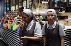 Unas monjas comiendo uvas tras haberlas comprado en el mercado municipal de Sao Paulo, ene 7, 2016. La tasa de la inflación anual de Brasil extendió su declive a mediados de abril tras la baja decretada en las tarifas de la electricidad, pero la reducción fue menor a lo esperado debido al salto en los precios de los alimentos.  REUTERS/Nacho Doce