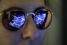 Экран с графиком движения акций отражается в очках инвестора. Европейские фондовые индексы укрепились вблизи трехмесячных максимумов в ходе торгов среды, поскольку значительная часть негативных эффектов от ослабления цен на нефть была нивелирована сильной отчетностью ряда компаний, а также подъемом акций банковского сектора. REUTERS/Regis Duvignau