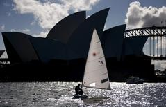 Australian Olympic team sailor Tom Burton sails his laser yacht during a training session in front of the Sydney Opera House in Sydney Harbour, Australia April 13, 2016.  REUTERS/David Gray
