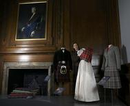 Gallery worker Caroline de Guitaut, curator at the royal collections trust, poses with part of the largest exhibition of The Queen's dresses and accessories ever shown in Scotland at the Palace of Holyroodhouse, Scotland April 20, 2016. REUTERS/Russell Cheyne