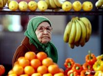 An elderly Russian woman looks longingly at the display of expensive fruit and vegetable in one of the Moscow markets on May 11. Rising inflation and high food prices have hurt pensionaires - RTXFEN1
