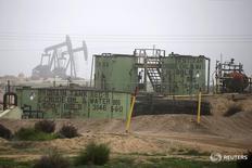 Станки-качалки под Бейкерсфилдом, Калифорния 17 января 2015 года. Цены на нефть снизились на волатильных торгах понедельника после выхода данных о росте запасов на распределительном центре в американском Кушинге, однако слабый доллар сдерживает падение котировок, сохранив их вблизи максимума пяти месяцев. REUTERS/Lucy Nicholson