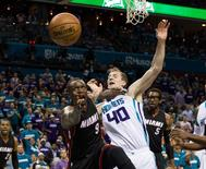 Miami Heat forward Luol Deng (9) pushes off Charlotte Hornets center Cody Zeller (40) while going for a lose ball in the second half in game four of the first round of the NBA Playoffs at Time Warner Cable Arena. The Hornets defeated the Heat 89-85. Mandatory Credit: Jeremy Brevard-USA TODAY Sports