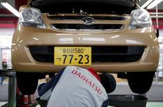 An engineer works under a Daihatsu Motor Co.'s Move vehicle at the company's dealership in Tokyo November 11, 2014.  REUTERS/Yuya Shino