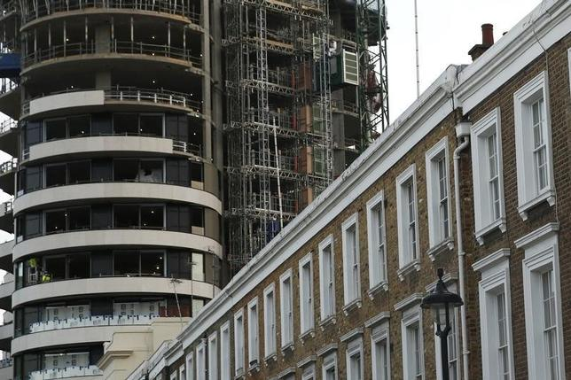 An apartment block is constructed behind a row of traditional properties in central London in this December 11, 2014 file photo. REUTERS/Luke MacGregor