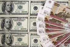 Рублевые и долларовые купюры в Сараево 9 марта 2015 года. Рубль торгуется в плюсе вокруг отметки 65 за доллар, отражая относительный баланс продаж валюты под уплату налога на прибыль и спрос на неё перед майскими праздниками, но при этом пытается удержать доллар ниже нее, отталкиваясь от возобновившей рост нефти. REUTERS/Dado Ruvic