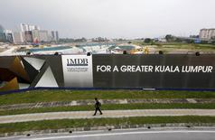 A man walks past a 1 Malaysia Development Berhad (1MDB) billboard at the funds flagship Tun Razak Exchange development in Kuala Lumpur, in this March 1, 2015 file photo.  REUTERS/Olivia Harris