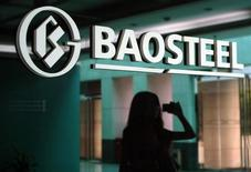 A woman is reflected on a wall with a company logo of Baosteel Group at an office in Shanghai, July 24, 2011. REUTERS/Stringer