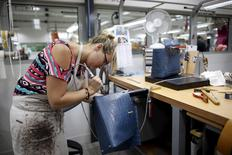 A craftswoman works on a Kelly bag at the luxury goods Hermes factory in Seloncourt October 4, 2013. REUTERS/Benoit Tessier/File Photo