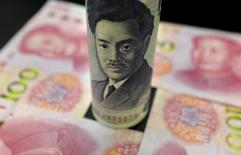 Банкнота в 1000 иен и банкноты в 100 юаней. Иена продолжила набирать силу в пятницу благодаря сильному росту после неожиданного решения Банка Японии воздержаться от расширения программы стимулирования, поднявшись до пика 18 месяцев к доллару и готовясь показать рекордный недельный рост с финансового кризиса 2008 года.  REUTERS/Jason Lee