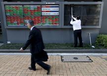 Foto de archivo de un hombre limpiando un panel electrónico afuera de una correduría en Tokio, Japón. 6 de abril de 2016. El yen tocó el viernes un máximo de 18 meses luego de que los inversores apostaron que el Banco de Japón no ofrecerá un nuevo estímulo a la economía, lo que debilitaba a la mayoría de los mercados bursátiles de Asia. REUTERS/Issei Kato/Files