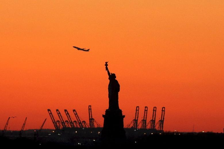 A plane is seen during take off in New Jersey behind the Statue of Liberty in New York's Harbor as seen from the Brooklyn borough of New York February 20, 2016. REUTERS/Brendan McDermid/File Photo
