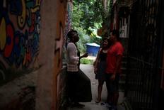 Solange, a worker at Pousada Favelinha hostel, talks to guests outside the hostel in Pereira da Silva favela, in Rio de Janeiro, Brazil, April 29, 2016. REUTERS/Pilar Olivares