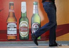 Мужчина проходит мимо входа в штаб-квартиру Anheuser-Busch InBev в Лёвене 3 марта 2011 года. Крупнейшая в мире пивоваренная компания Anheuser-Busch InBev, готовящаяся купить ближайшего конкурента SABMiller, отчиталась о не дотянувшей до ожиданий прибыли в первые три месяца финансового года из-за сложных условий в охваченной кризисом Бразилии. REUTERS/Yves Herman