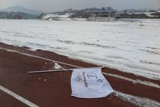 A flag bearing the logo of 2018 Winter Olympic Games lies on the ground at the proposed site of the Olympic Stadium near the Alpensia Resort in the mountain cluster of PyeongChang February 10, 2015.   REUTERS/Pawel Kopczynski