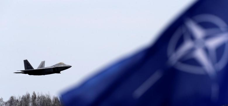 NATO flag flutters as U.S. Air Force F-22 Raptor fighter flies over the military air base in Siauliai, Lithuania, April 27, 2016. REUTERS/Ints Kalnins