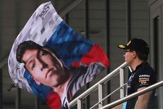 Formula One - Russian Grand Prix - Sochi, Russia - 30/4/16 - A spectator looks at a flag with the picture of Red Bull F1 driver Daniil Kvyat of Russia. REUTERS/Yuri Kochetkov/Pool