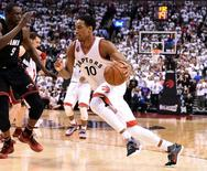 Toronto Raptors guard DeMar DeRozan (10) dribles the ball past Miami Heat forward Luol Deng (9) in game two of the second round of the NBA Playoffs at Air Canada Centre. The Raptors won 96-92.  Mandatory Credit: Dan Hamilton-USA TODAY Sports