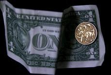 Монета в 1 австралийской доллар на фоне доллара США. Доллар немного снижается по отношению к корзине основных мировых валют в ходе торгов пятницы, но по-прежнему может продемонстрировать рост по итогам недели, пока инвесторы ждут публикации данных о занятости в США за апрель.  REUTERS/David Gray/Illustration