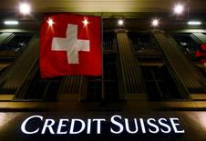 The logo of Swiss bank Credit Suisse is seen below the Swiss national flag at a building in the Federal Square in Bern, Switzerland, May 15, 2014. REUTERS/Ruben Sprich/File Photo