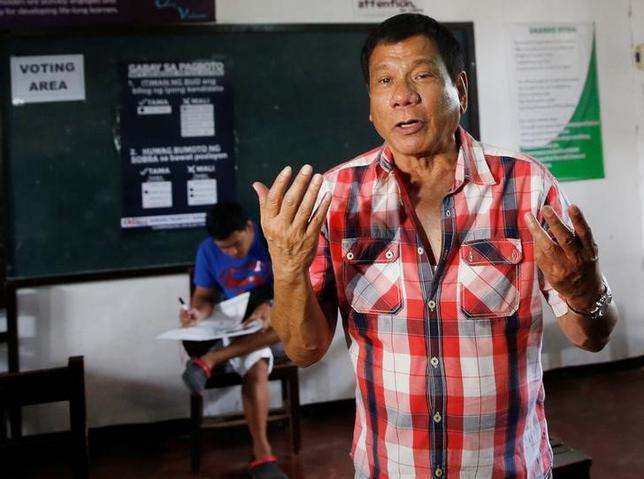 Presidential candidate Rodrigo ''Digong'' Duterte gestures as he speaks to reporters before casting his vote at a polling precinct for national elections at Daniel Aguinaldo National High School in Davao city in southern Philippines, May 9, 2016.    REUTERS/Erik De Castro