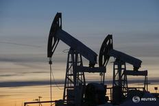 Станки-качалки на Имилорском месторождении Лукойла под Когалымом 25 января 2016 года. Цены на нефть незначительно меняются во вторник, поскольку рост запасов и угроза перенасыщения рынка нефтепродуктов перевесили сбои поставок в Канаде и других регионах, которые сократили производство более чем на 2 миллиона баррелей в день. REUTERS/Sergei Karpukhin/Files