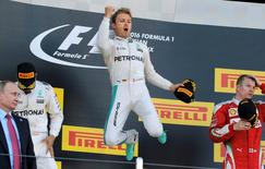 Mercedes F1 driver Nico Rosberg of Germany (C) jumps on the podium as he celebrates victory during the Russian Grand Prix.   REUTERS/Maxim Shemetov