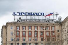 Логотип Аэрофлота на крыше здания в Москве.  Пассажиров лондонского аэропорта Хитроу встречает большой рекламный щит с видом ночного Шанхая и стюардессой в оранжевой форме, приглашающей лететь рейсами российского Аэрофлота и его партнеров в Азию через Москву. REUTERS/Maxim Zmeyev
