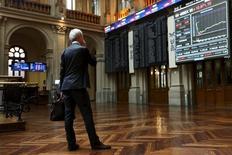 El Ibex-35 recuperaba el viernes a mediodía la mayor parte de sus pérdidas iniciales, respaldado por la reacción favorable en el mercado a una serie de resultados de empresas. En la imagen de archivo, un hombre observa las pantallas en la Bolsa de Madrid  el 29 de junio de 2015. REUTERS/Susana Vera