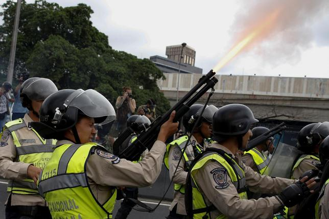 A riot policeman fires into the air during clashes with opposition supporters at a rally demanding a referendum to remove President Nicolas Maduro in Caracas, Venezuela, May 11, 2016. REUTERS/Carlos Garcia Rawlins