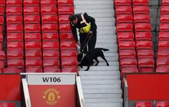 Policial com cão farejador após esvaziamento do estádio Old Trafford, na Inglaterra.    15/05/2016    Reuters / Andrew Yates Livepic