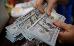 Сотрудник банка пересчиывает долларовые купюры. Американский доллар немного снизился в ходе торгов в Азии во вторник, в то время как австралийский доллар резко укрепился после выхода протокола заседания австралийского регулятора, который уменьшил ожидания снижения процентной ставки. REUTERS/Kham