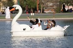 A woman takes a selfie with her children as they ride a boat at Aspire Park in Doha, Qatar April 8, 2016. REUTERS/Naseem Zeitoon